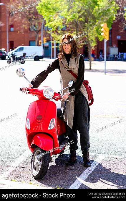 Happy cheerful girl driving scooter through city street