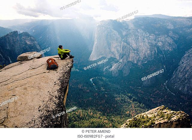 Man sitting at top of mountain, overlooking Yosemite National Park, California, USA