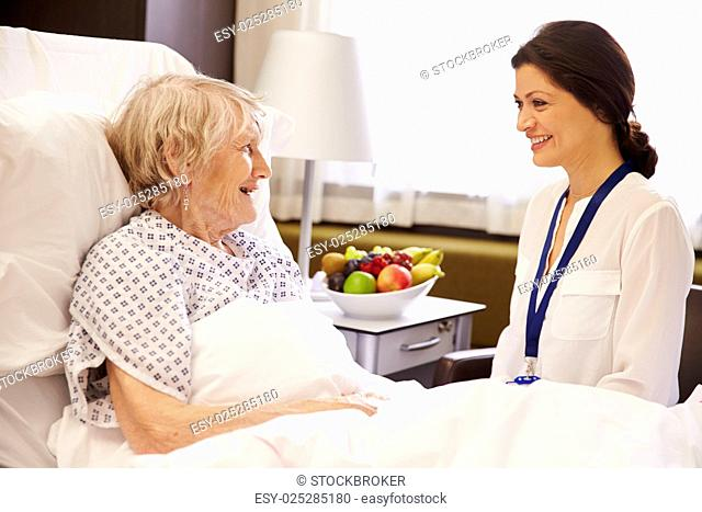 Doctor Talking To Senior Female Patient In Hospital Bed