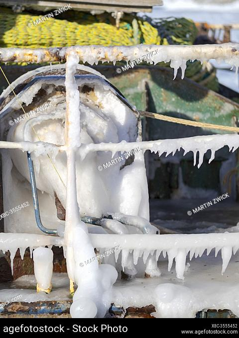 Icicles on reeling of a trawler. Winter in the frozen harbour of town Ilulissat on the shore of Disko Bay. America, North America, Greenland, Denmark