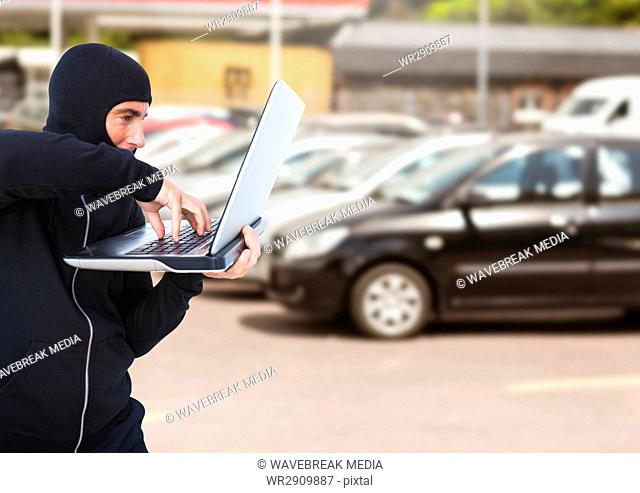 Criminal in hood with laptop in front of cars