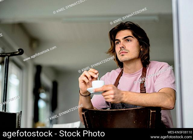 Thoughtful owner holding coffee cup while sitting on chair in cafe