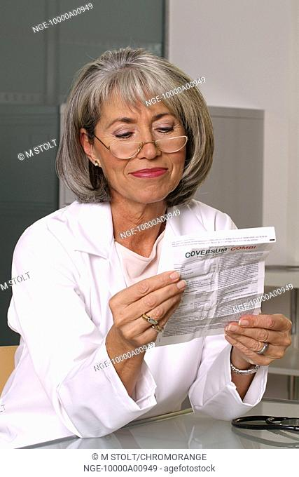 gray-haired female doctor reading patient information leaflet