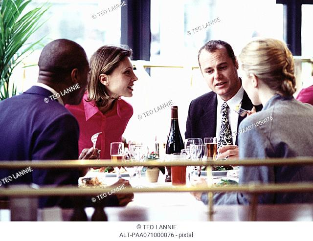 Business people sitting at table, eating, close up