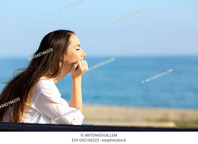 Side view portrait of a woman relaxing mind on the beach