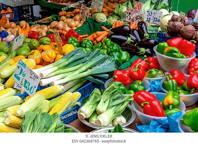 Peppers, corn, leek and other vegetables for sale at a market in Brixton, London