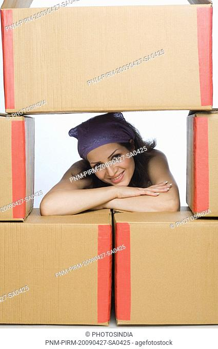 Portrait of a woman leaning on cardboard boxes