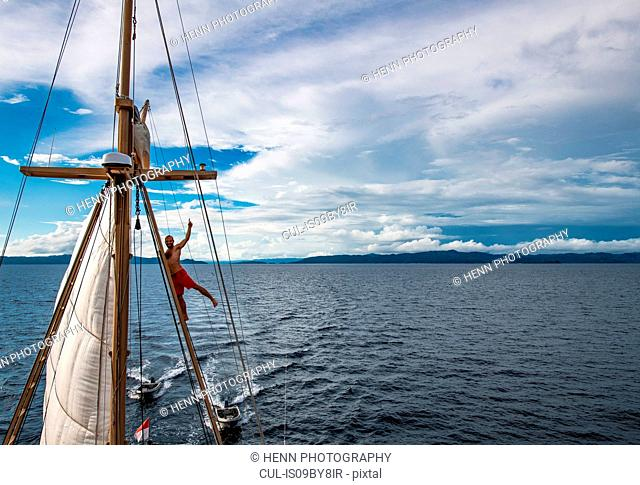 Man climbing up sail boat mast in the calm waters of Raja Ampat, Sorong, Nusa Tenggara Barat, Indonesia