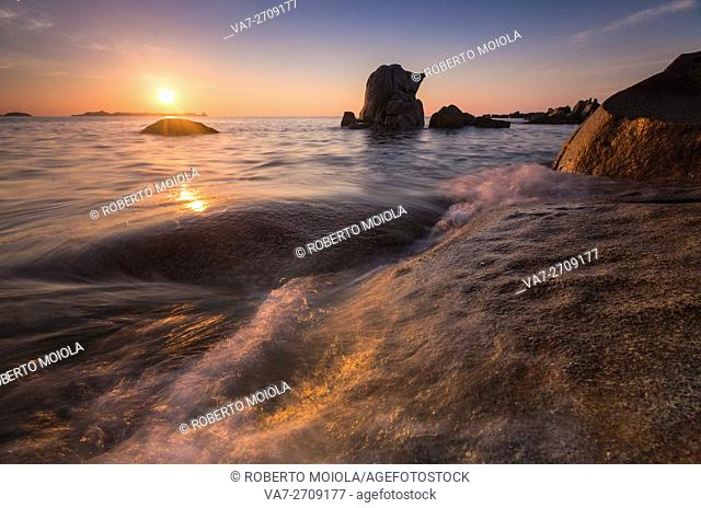 Waves crashing on cliffs under the fiery sky at sunrise Punta Molentis Villasimius Cagliari Sardinia Italy Europe