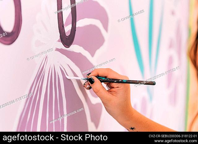 A close up of a painter at work and painting florals on a wall