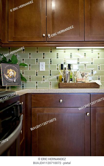 Bottles with glasses and cook book on kitchen counter below cabinets at home; San Marcos; California; USA