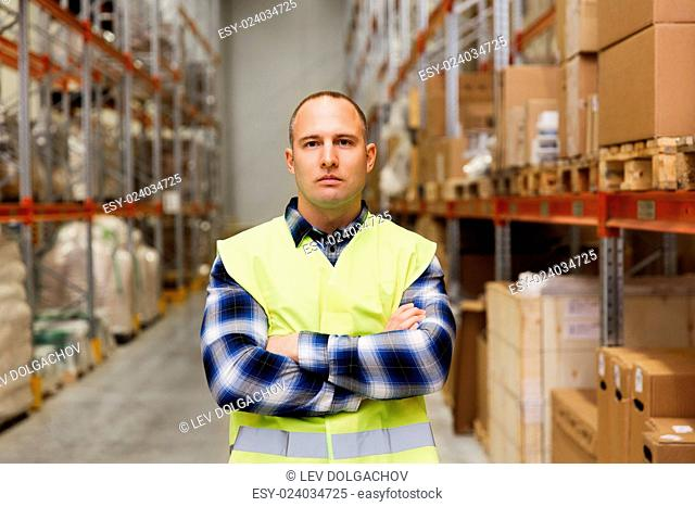 wholesale, logistic, people and export concept - man in reflective safety vest at warehouse