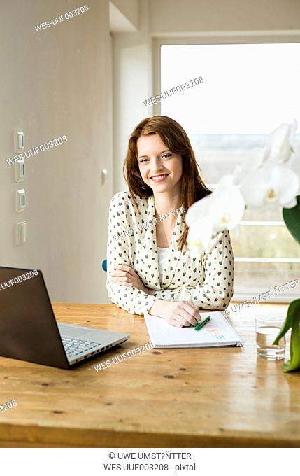 Smiling young woman with laptop at wooden table