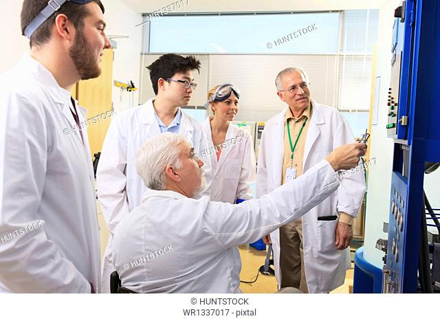 Professors explaining operation of water ultra purification system to engineering students in a laboratory
