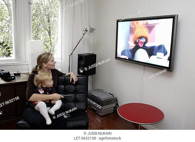 A mother and a little child watch a children's programme on a large flat TV screen at home