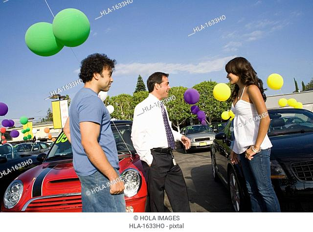 Young couple talking to car salesman