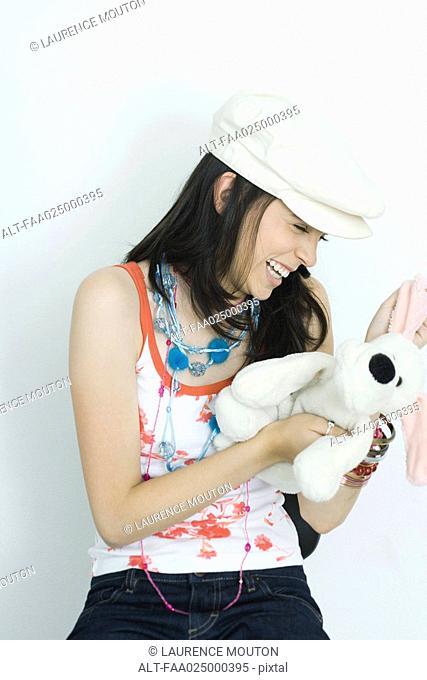Teenage girl holding stuffed toy, laughing