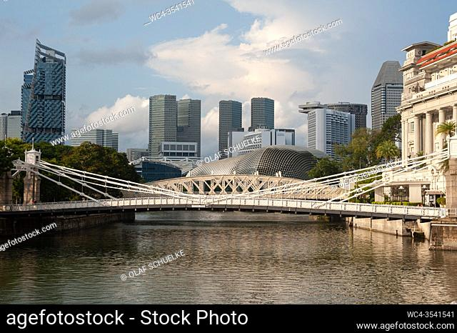 Singapore, Republic of Singapore, Asia - Cityscape of the Cavenagh Bridge spanning the Singapore River with skyscrapers of the downtown district in the backdrop...
