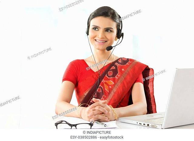 Indian businesswoman wearing headset and smiling