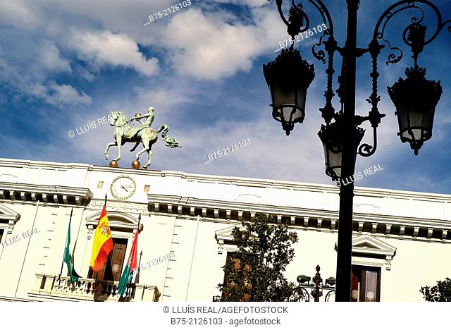 Detail of the facade of the Granada's town hall with street lamp in foreground and flags on the balcony. Province of Granada, Andalucia, Spain