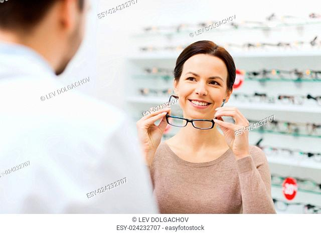 health care, people, eyesight and vision concept - happy woman choosing glasses with optician at optics store