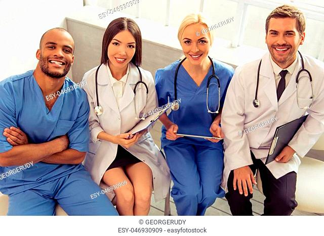 Group of medical doctors of different nationalities and genders with folders and tablet is looking at camera and smiling, sitting in office