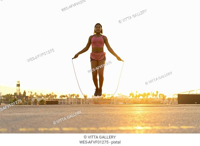 Spain, Barcelona, young black woman skipping rope at sunrise