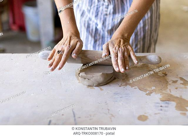 Woman Hand Cutting Clay With Thread In Ceramic Workshop