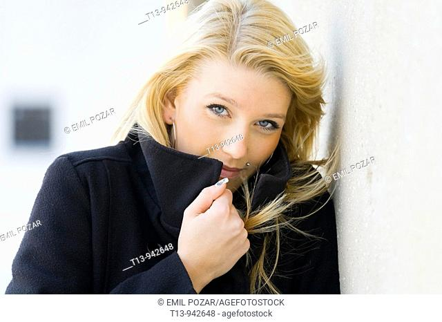 Young woman portrait in Black coat, it's cold and windy