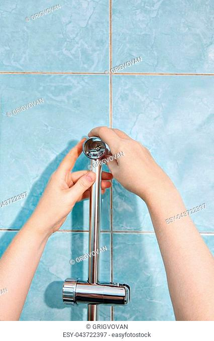 Close-up handyman hands, install vertical holder for shower on wall
