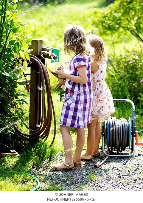 Girls washing carrots at pump