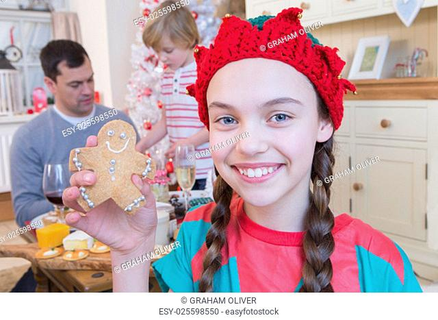 Young Girl dressed as an Elf at Christmas Time with Dad and Brother in the background. She is smiling at the Camera and holding up a decorated Gingerbread Man