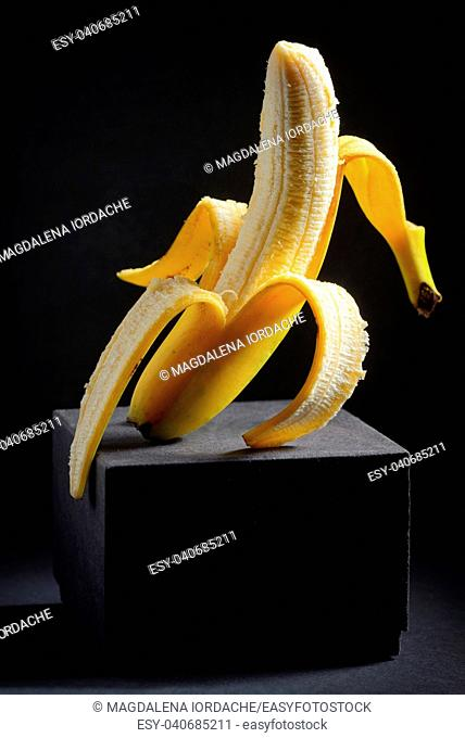 Vertical peeled banana on black background