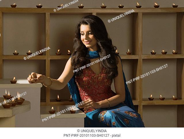 Woman decorating oil lamps in Diwali festival