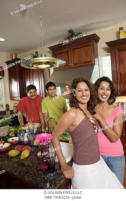 Indian family in kitchen preparing food