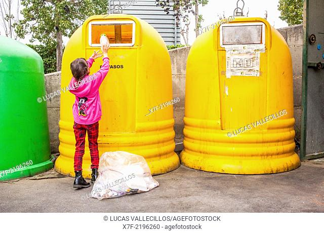 Containers of plastic for waste separation. Girl places plastic into a collector to recycle,recycling center