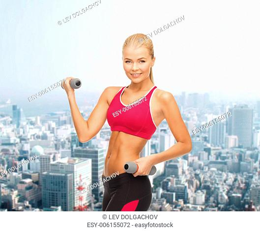 fitness and healthcare concept - young sporty woman with light dumbbells