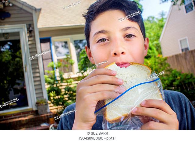Portrait of cute boy eating sandwich in garden