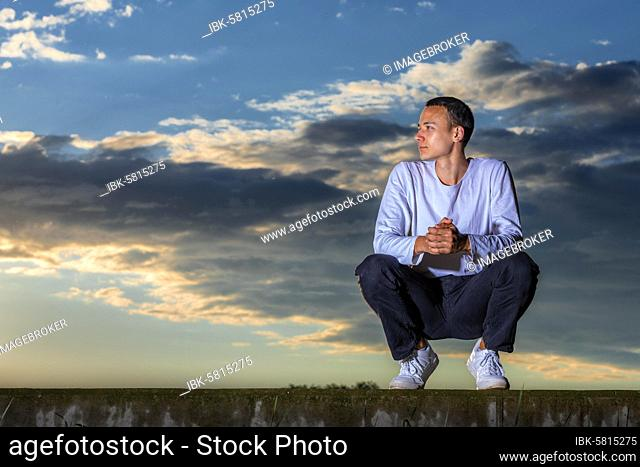 Man, 21 years, sitting, in the sunset, Remstal, Baden-Württemberg, Germany, Europe