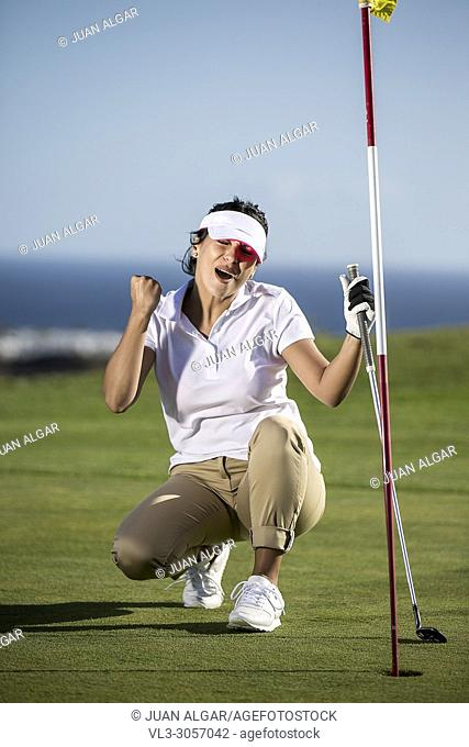 Brunette holding driver and doing fist up celebrating goal while playing golf on green course