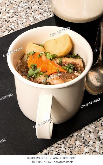 dublin coddle, an irish specialty in a mug on slate