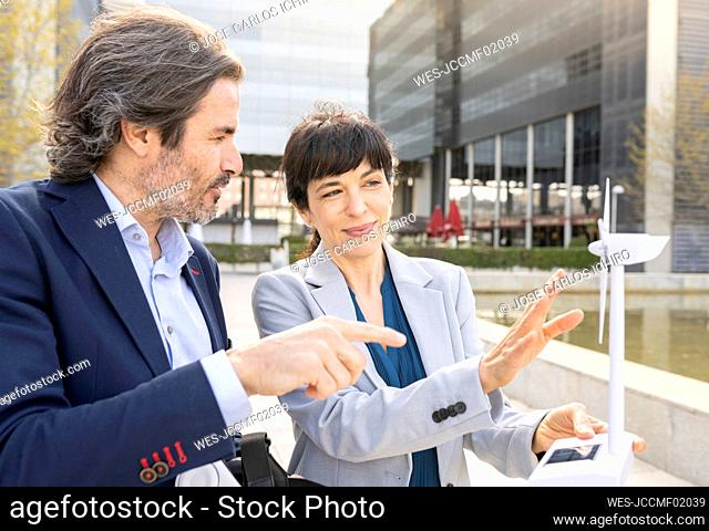 Mature female engineer explaining wind turbine model with male colleague in park
