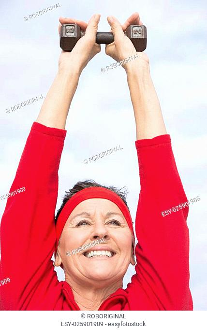Portrait beautiful mature woman showing active retirement, excercising with weights arms up outdoor, positive, confident, energetic, happy smiling
