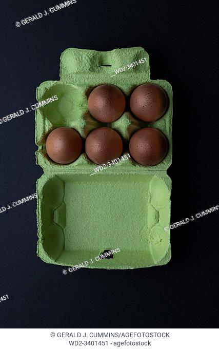 Five Brown eggs in a green cardboard carton. Dark Background