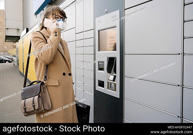 Woman on the phone wearing face mask and gloves near a parcel terminal
