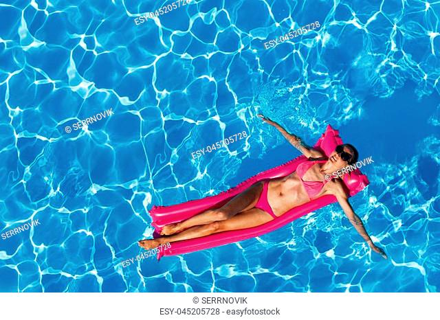 Top view portrait of relaxed woman in pink bikini and sunglasses floating on inflatable mattress in swimming pool