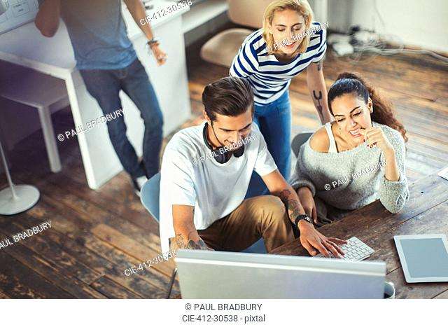 Creative young business people working at computer in office