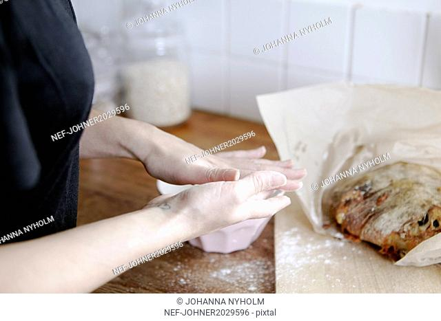 Hands with bowl of flour, loaf of bread on worktop