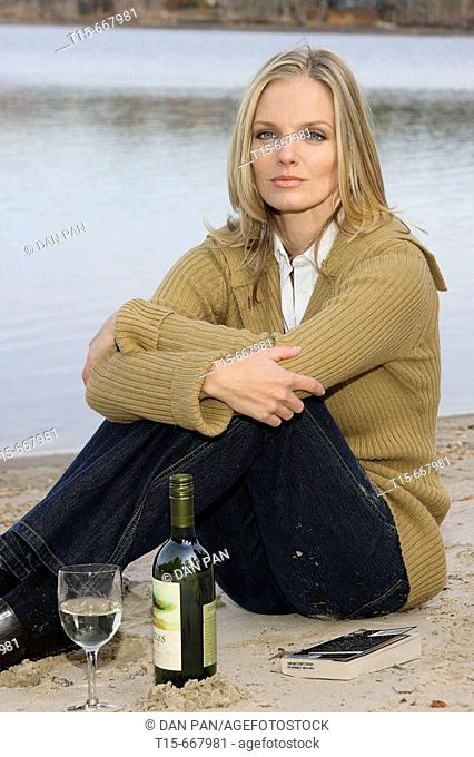 Blond woman in her 20's 30's sitting by a lake with wine bottle, glass and a book looking sad, tired