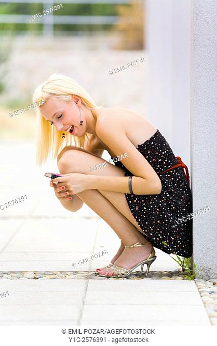 Pretty young woman excited with cellular phone